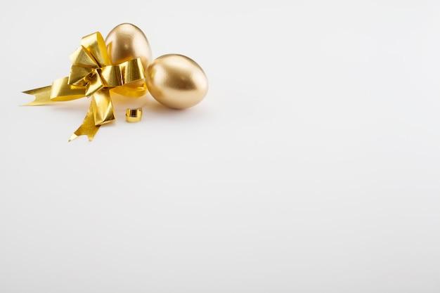 金の卵は、コピースペース付きの金の弓で飾られています。イースターのコンセプトの背景。