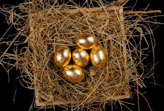 Золотые яйца в гнезде на виде сверху черной поверхности. концепция пасхи.