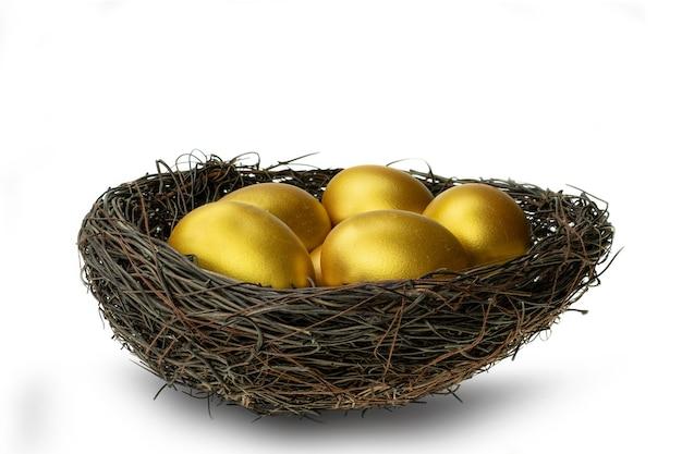 Золотые яйца в декоративном гнезде, изолированные на белом фоне