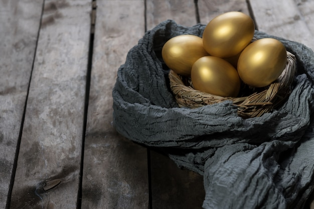 어두운 빈티지 나무 테이블에 둥지에서 황금 알