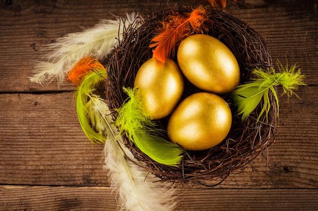 Золотые яйца в гнезде на деревянном фоне с копией текста