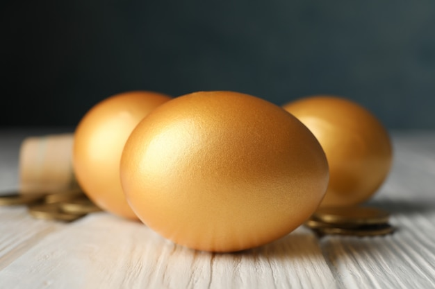 Golden eggs and money on wooden surface