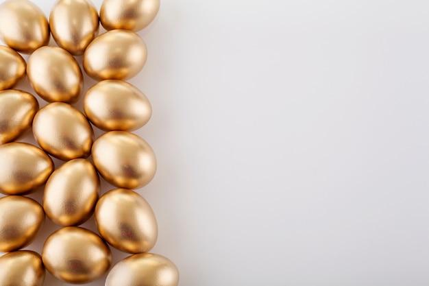 テキストのための場所で、白い背景の上の黄金の卵。イースターのコンセプトです。