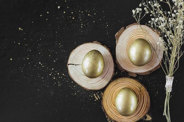 Золотые яйца на досках возле цветов
