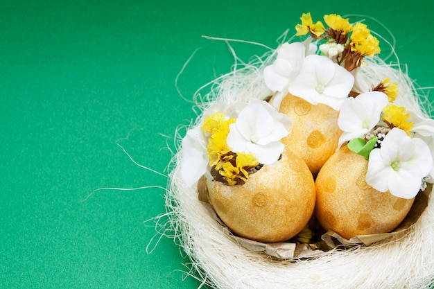 Golden eggs with flowers in a nest on green surface