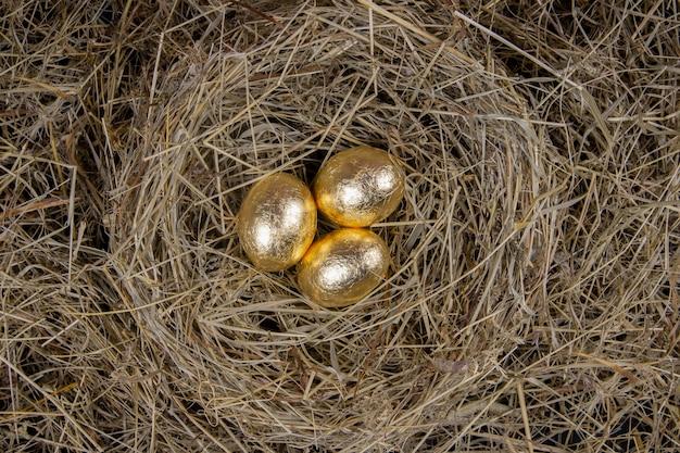 Золотые яйца с видом сверху гнездо. концепция пасхи.