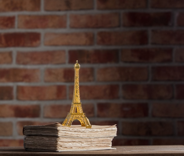 Golden eiffel tower souvenir and old books