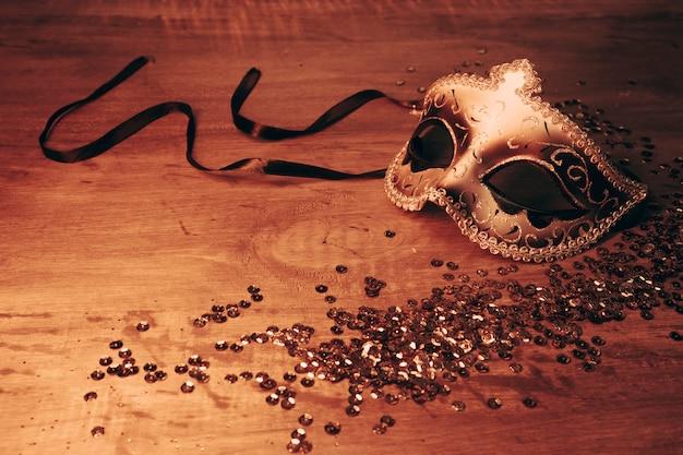 빛나는 장식 조각으로 나무 책상에 황금 우아한 여성 카니발 마스크