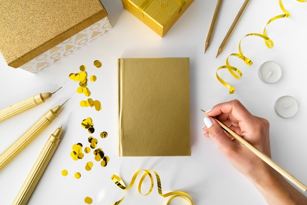 Golden elements with notebook and hand