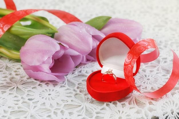 심장 모양의 상자와 꽃 튤립에 황금 약혼 반지
