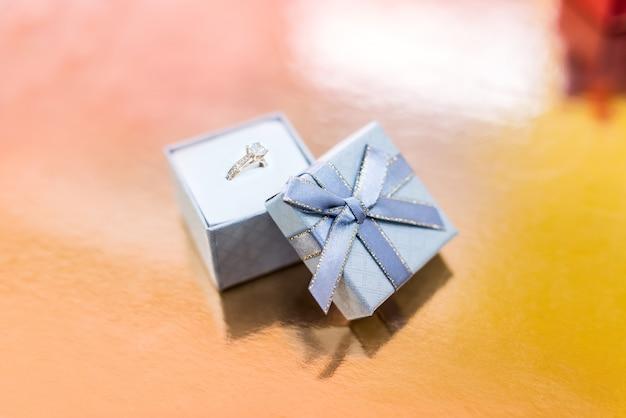 シルバーのギフトボックスに金色の婚約指輪