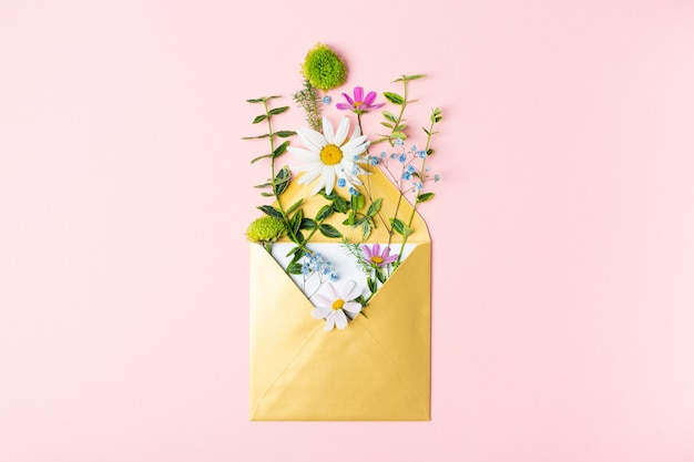 분홍색 배경에 아름다운 봄 정원 꽃이 있는 황금 봉투