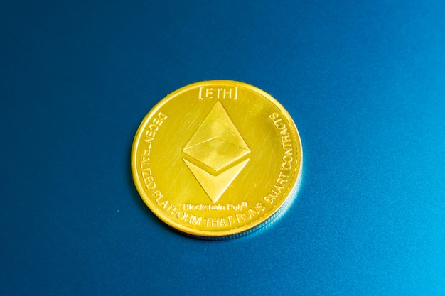 Golden ethereum coin with ethereum symbol on a laptop keyboard next to the enter key