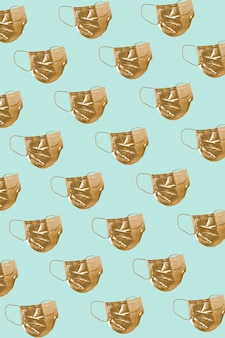 Golden face mask pattern on a green background