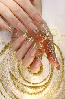 Golden fashion french manicure on long nails with gold glitter.