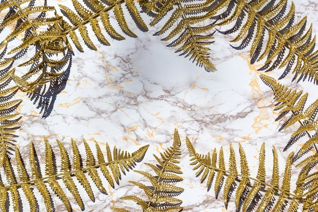 Golden fern leafs, palm frond on marble