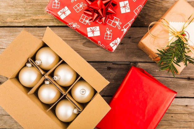 Golden festiveornaments in box with christmas presents