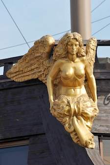A golden figure of a mermaid on the bow of the ship