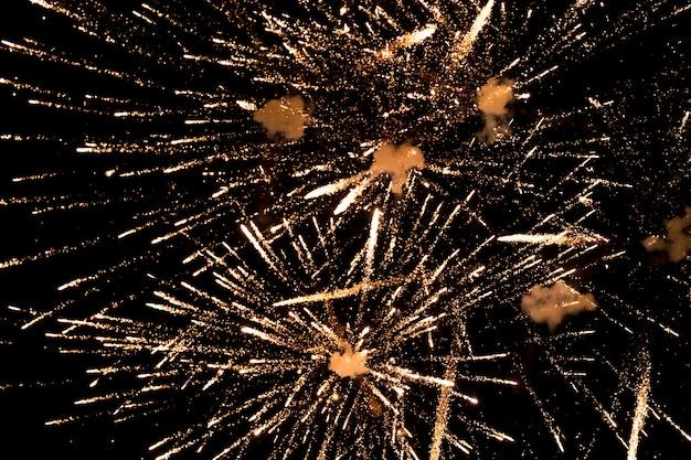 Golden fireworks on black sky