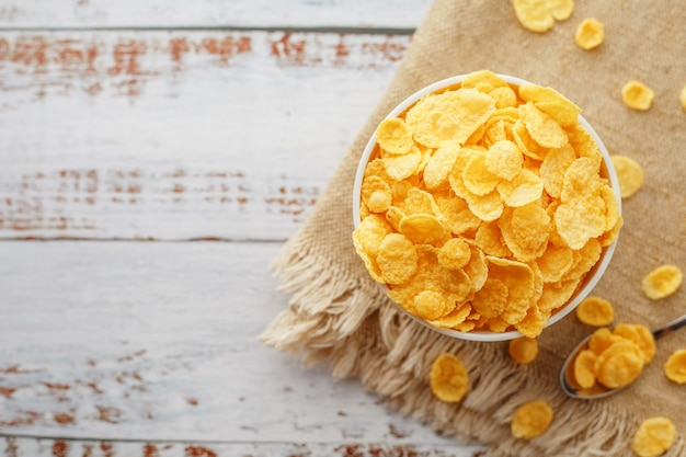 Golden flakes in a cup on burlap, on a light wooden table, next to a spoon.