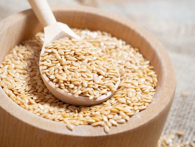 Золотые семена льна, льняное семя в деревянной ложке на старом деревенском фоне крупным планом, белый лен