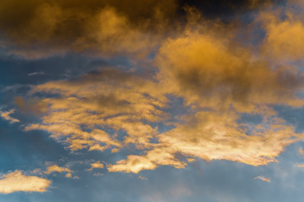 夕焼けの消える光線に照らされた金色のふわふわの雲と暗い雷雲の青い空
