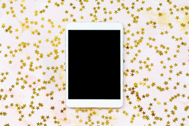 Golden foil stars confetti decoration and tablet on pink background. christmas celebration, winter and dreams concept. top view, flat lay, mock up