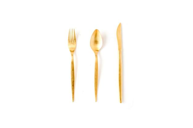 金色のフォーク、スプーン、ナイフは白で隔離