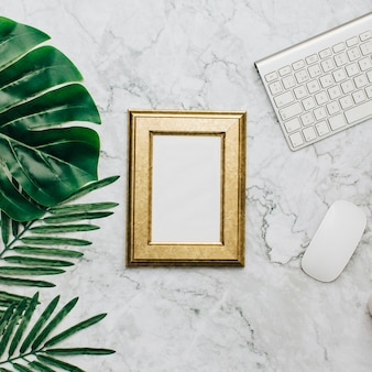 Golden frame on marble desktop and tropical leaves