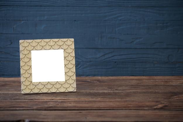 Золотая рамка на деревянном столе на синем деревянном фоне