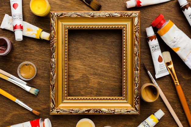 Golden frame surrounded by paint and brushes