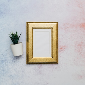 Golden frame with cactus over watercolor surface