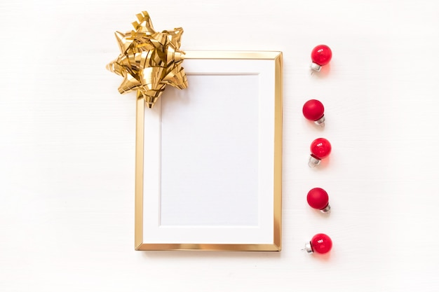 Golden frame with gold bow isolated on white background. winter minimalistic christmas fla