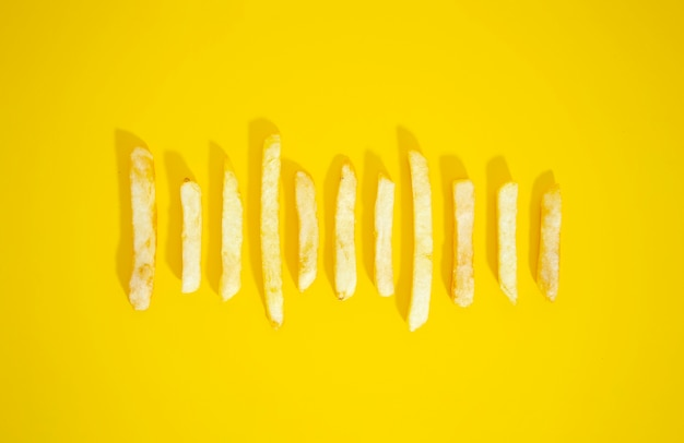 Golden french fries on yellow background