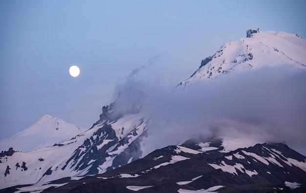 파란 시간에 먼 산 위로 떠오르는 황금 보름달 프리미엄 사진