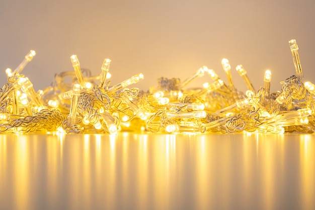 Golden garland of warm white lights on a table with reflection.