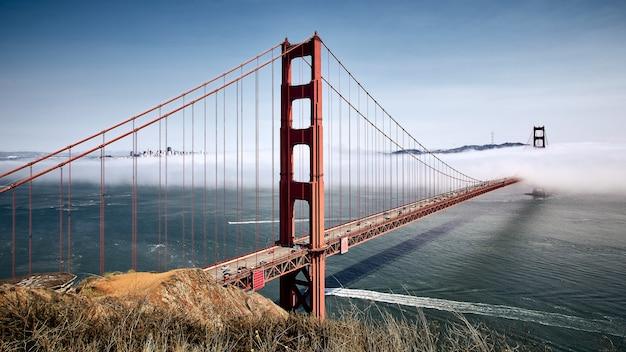 米国カリフォルニア州サンフランシスコの霧深い青い空を背景にしたゴールデンゲートブリッジ