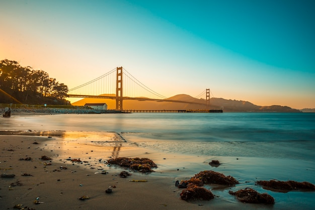 Golden gate of san francisco and its beautiful sunset from the beach. united states