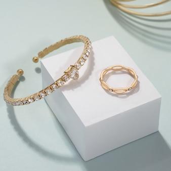Золотые браслеты из драгоценных камней с золотым кольцом на белом кубе