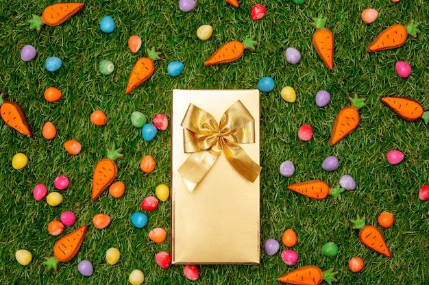 Золотая подарочная коробка и пасхальные яйца с морковью печенья на зеленой траве