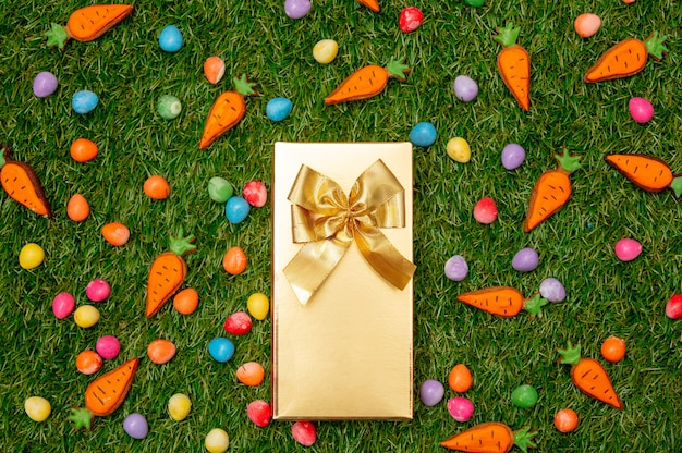 Golden gift box and easter eggs with cookie carrots on green grass