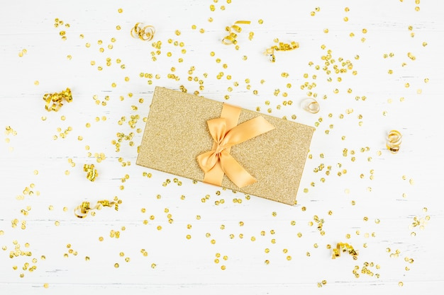 Golden gift box with confetti