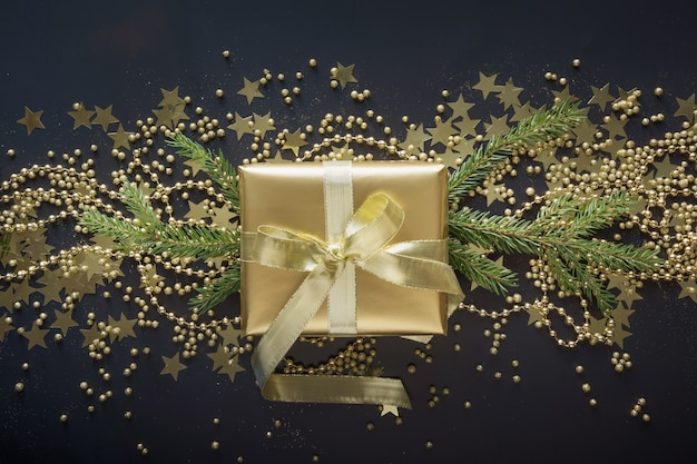 Golden gift box with gold ribbon on black background christmas present flat lay top view. festive banner. xmas pattern.