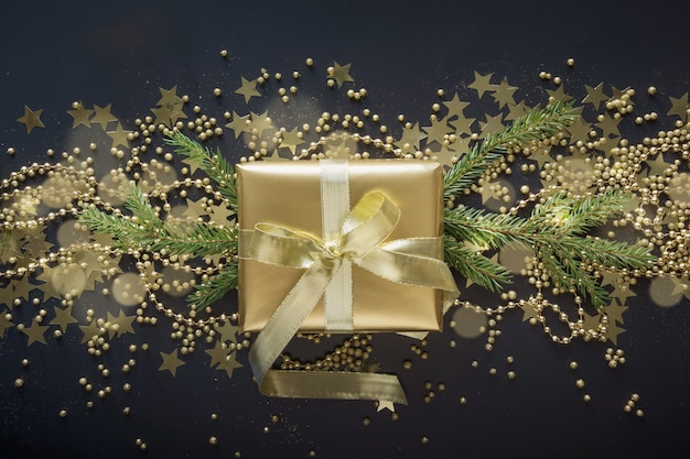 Golden gift box with gold ribbon on black