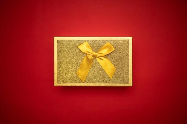 Золотой подарок на красном фоне, вид сверху подарочная коробка.