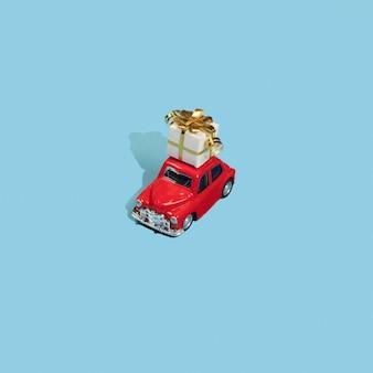 青い背景の屋根の赤いおもちゃの車の黄金の贈り物
