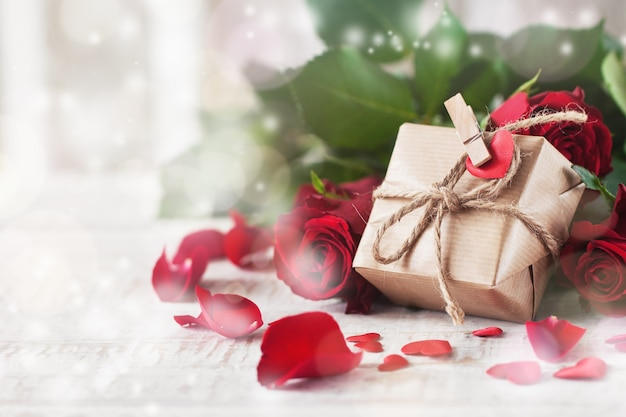 Золотой подарок покоится на розы
