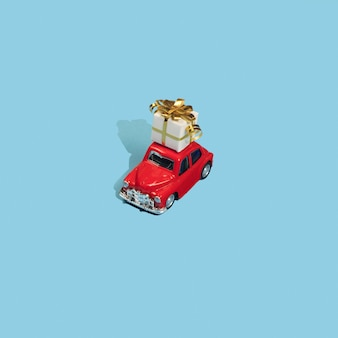Golden gift on roof red toy car on blue background