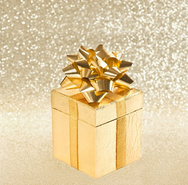 Golden gift with ribbon over shiny background