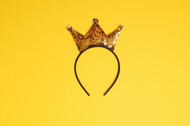Golden glitter crown headband on yellow background.